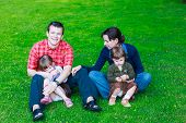 Happy Family Of Four Sitting On Grass