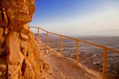 stock photo of bannister  - Limestone steep above desert with a safety bannister at sunset - JPG