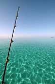 stock photo of fishing rod  - fishing rod over a turquoise lagoon - JPG