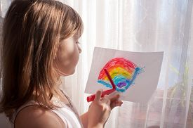 stock photo of grils  - Nice teen gril painting colorful rainbow near the window - JPG