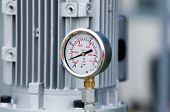 picture of vacuum pump  - Close up of metal manometer with machinery in background - JPG