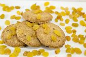 stock photo of baked raisin cookies  - Integral cookies and yellow raisins on white - JPG