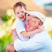 stock photo of grandpa  - portrait of happy grandpa and grandson embracing outdoors - JPG