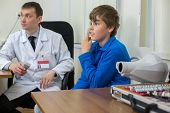 stock photo of infirmary  - teenager checks sight at the reception of an ophthalmologist - JPG