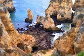 foto of lagos  - Scenic landscape showing a beautiful coast with steep large cliffs and the blue ocean water shot in Lagos Algarve Portugal - JPG