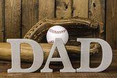 stock photo of baseball bat  - letters spelling dad in front of baseball bat and baseball in glove  on  wood background - JPG