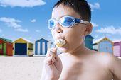 image of naked children  - Happy little child wearing swimming glasses on the coast while enjoying a yummy ice cream - JPG