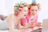 image of pajamas  - Young beautiful girls wearing pajamas and colorful hair rollers lying on the bed laughing and looking at laptop at home party in the light room - JPG