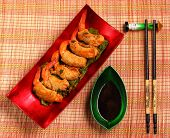 pic of deep  - traditional Vietnam deep fried shrimp and pork rolls in breadcrumbs served on a traditional bamboo place mat - JPG