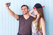 picture of selfie  - two women and man friends taking selfie together wearing summer clothes  jeans shorts jeanswear street urban casual style having fun - JPG
