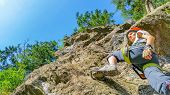stock photo of mountain-climber  - Young woman climber on via ferrata in Alps, Zillertal, Austria