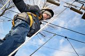 foto of suspension  - little boy going on suspension way in the equipment and looking down - JPG