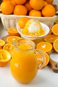 stock photo of pitcher  - Freshly squeezed orange juice in the pitcher and oranges on the table - JPG