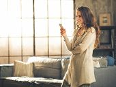 image of comfort  - Seen in profile a brunette woman in comfortable clothing is standing in a loft living room looking down at her phone and smiling - JPG