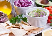 foto of nachos  - Guacamole in porcelain Bowl with mexican Tortilla Chips nachos and Ingredients - JPG