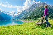 picture of mountain-high  - A young mountaineer stands beside an azure mountain lake on the background of the high peaks of the Alps - JPG