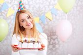 foto of cone  - Portrait of a young beautiful blond girl wearing cone cap holding a red plate with birthday cake with candles in the light decorated room - JPG