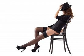 stock photo of stocking-foot  - Sexy woman in black stockings and a hat sitting on a chair on a white background - JPG