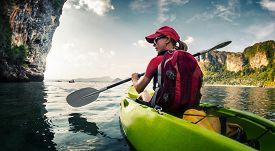 pic of kayak  - Young lady paddling the kayak in the calm bay with limestone mountains - JPG
