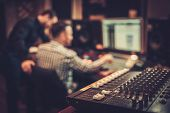 Постер, плакат: Sound engineer and producer working together at mixing panel in the boutique recording studio