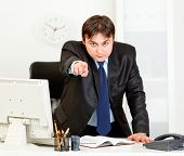 Angry modern businessman standing at office desk and pointing finger on you