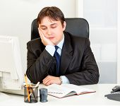 Bored modern businessman sitting at desk in office
