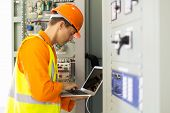 Постер, плакат: experienced electrician working in power plant control room