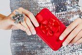 Caixa de presente vermelha nas mãos da mulher.