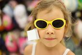Portrait Of Little Girl Trying Sunglasses With Yellow Rim In Store, Shallow Depth Of Focus