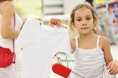 Little Girl Sitting In Store Cart And Holding Hanger With White Shirt, Looking At Camera