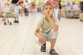Little Boy Sitting Alone On Hunkers In Big Store, Chin On Hand, Looking Up