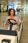 Young Beautiful Woman In White Wear Riding On Electric Car In Airport