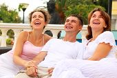 Three Friends Sitting Together On Couch Outdoors And Laughing, Focus On Man