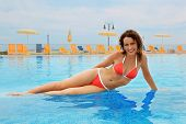 Beautiful Young Woman In Red Bathing Suit Sitting In Pool