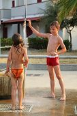 Little Brother And Sister Are Taking Outdoor Shower After Swim, Focus On Boy