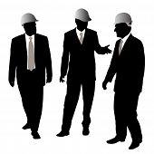 Three Businessmen Architects Or Engineers With Protective Helmet