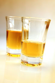 stock photo of mezcal  - Two shooter glasses with tequila ready to drink - JPG