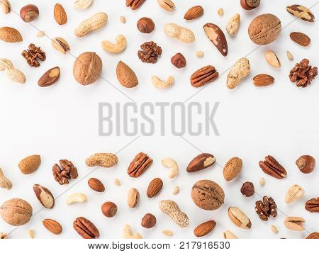 poster of Pattern of nuts mix with copy space. Various nuts isolated on white. Pecan, macadamia, brazil nut, walnut, almonds, hazelnuts, pistachios, cashews, peanuts, pine nuts. Top view or flat-lay. Copy space