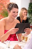woman looking at the menu at a restaurant