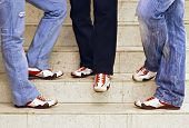 Men's Feet In Sneakers Standing On The Stairs