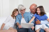 Senior people with grand kids using electronic tablet