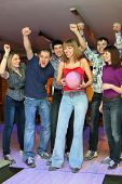 Woman prepares for throw  ball in bowling and friends it encourage, focus on girl in center