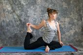 Woman Doing Yoga Posture Kapotasana Or Pigeon Pose Variation 2