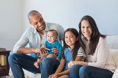 Portrait of happy multiethnic family sitting at home. Smiling couple with kids sitting on couch and  poster