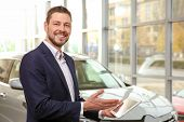 Handsome car salesman with tablet computer in dealership centre poster