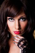Beautiful brunette girl with fine art lacy manicure on black