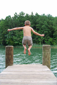 picture of dock a lake  - little boy jumping off dock into water - JPG