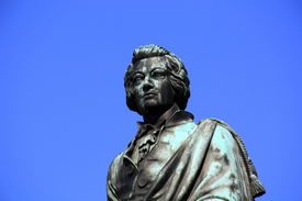 stock photo of mozart  - statue monument of Mozart with blue sky - JPG