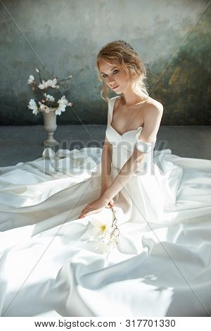 poster of Girl In A Chic Long Dress Sitting On The Floor. White Wedding Dress On The Bride's Body. Beautiful L