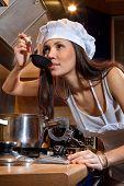 Portrait of sexy Hausfrau gefesselt von Handschellen in eine Pfanne. She Verkostung Teller in der Küche